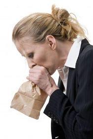Mujer que respira en la bolsa de papel para el tratamiento de la hiperventilación